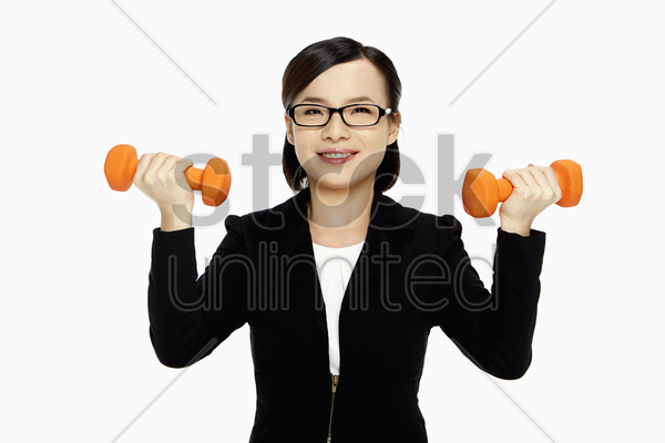 cheerful businesswoman lifting up dumbbells stock photo