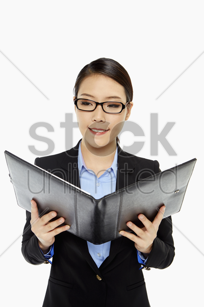 cheerful businesswoman reading notes from a folder stock photo