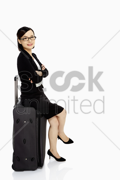 cheerful businesswoman sitting on a luggage bag stock photo