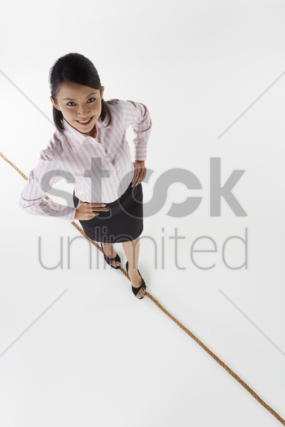 cheerful businesswoman walking on a tightrope stock photo