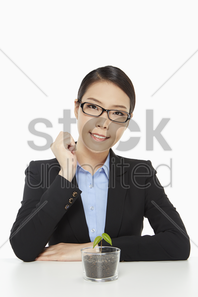 cheerful businesswoman with a small plant stock photo