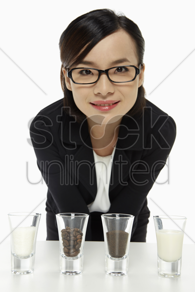 cheerful businesswoman with an assortment of shot glasses stock photo