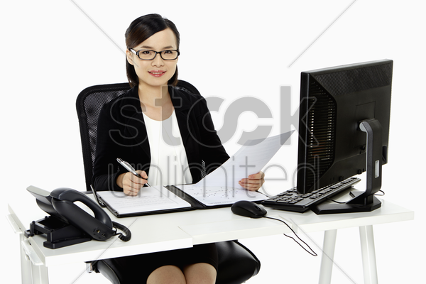 cheerful businesswoman writing down notes stock photo