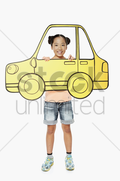 cheerful girl holding up a cardboard car stock photo