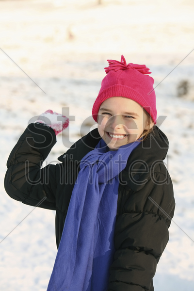 cheerful girl playing with snowball stock photo