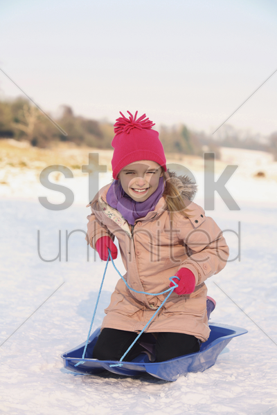 cheerful girl riding on sled stock photo