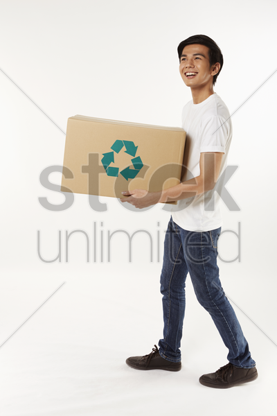 cheerful man carrying a recyclable cardboard box stock photo