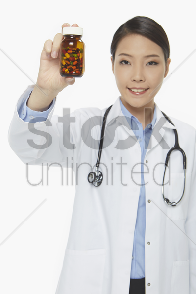 cheerful medical personnel holding up a bottle of pills stock photo