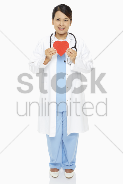 cheerful medical personnel holding up a red heart stock photo