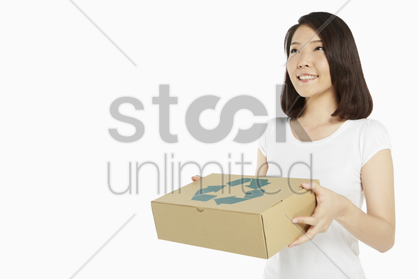 cheerful woman carrying a recyclable cardboard box stock photo