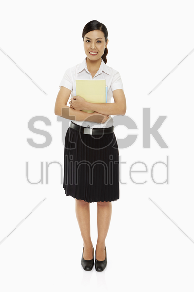 cheerful woman carrying books stock photo