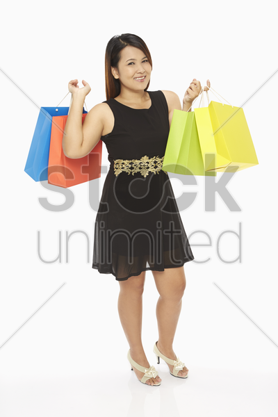 cheerful woman carrying colorful paper bags stock photo