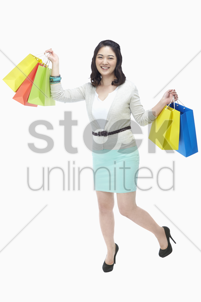 cheerful woman carrying paper bags stock photo