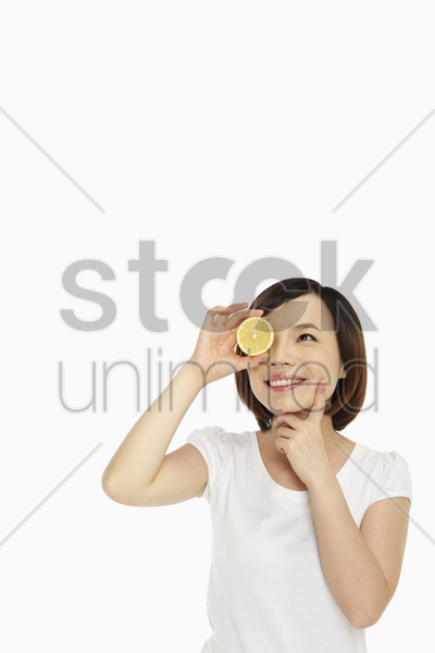 cheerful woman covering her eye with a lemon stock photo
