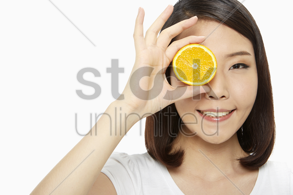 cheerful woman covering her eye with an orange stock photo