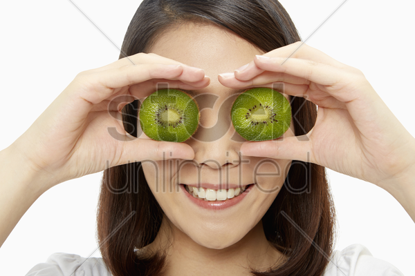 cheerful woman covering her eyes with a kiwi stock photo