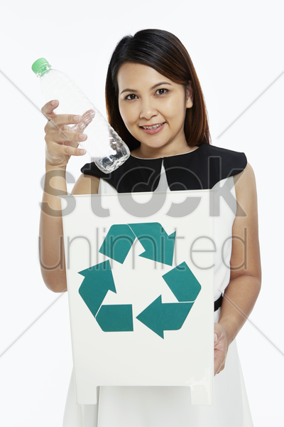 cheerful woman discarding a plastic bottle into a recycle bin stock photo