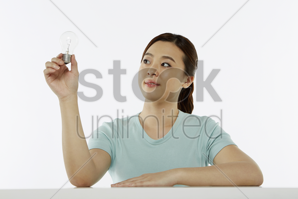cheerful woman holding a light bulb stock photo