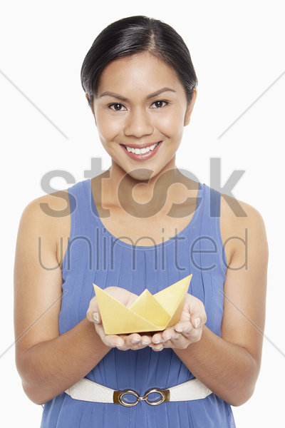 cheerful woman holding a paper boat stock photo