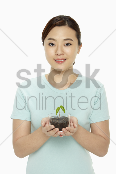 cheerful woman holding a small potted plant stock photo