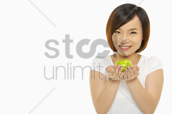 cheerful woman holding an apple stock photo