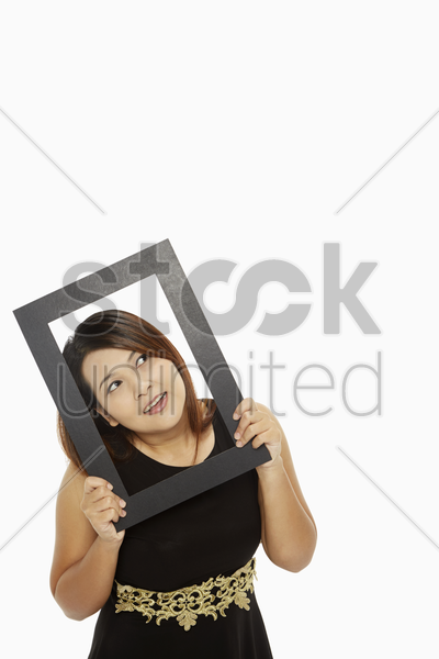 cheerful woman holding up a black picture frame stock photo