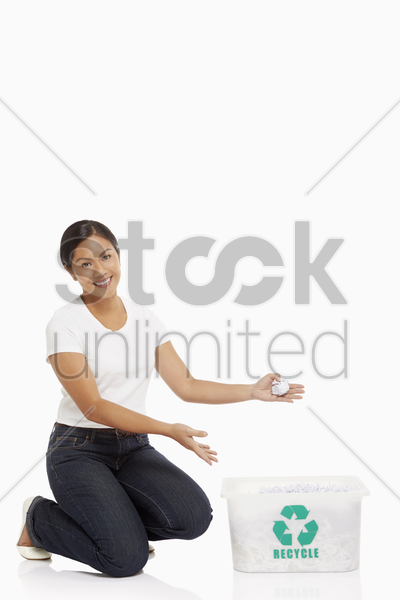 cheerful woman holding up a crushed piece of paper stock photo