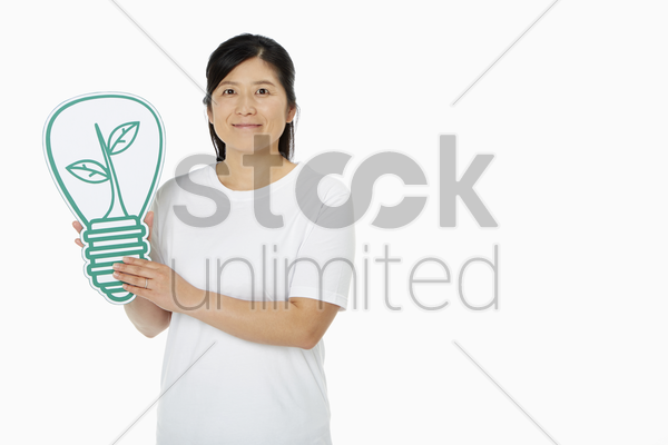 cheerful woman holding up a cut out light bulb stock photo