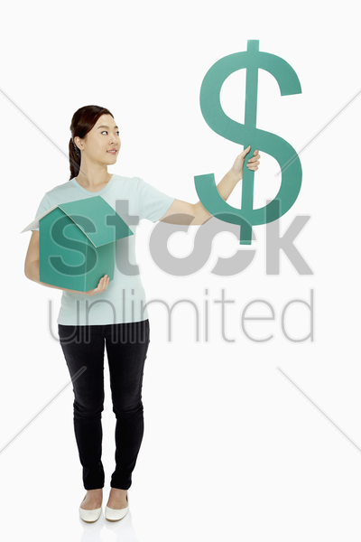 cheerful woman holding up a dollar sign and a cardboard house stock photo