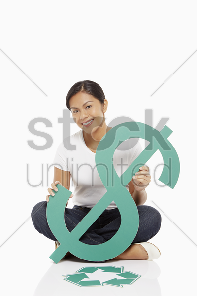 cheerful woman holding up a dollar sign, with recycle logo placed on floor stock photo