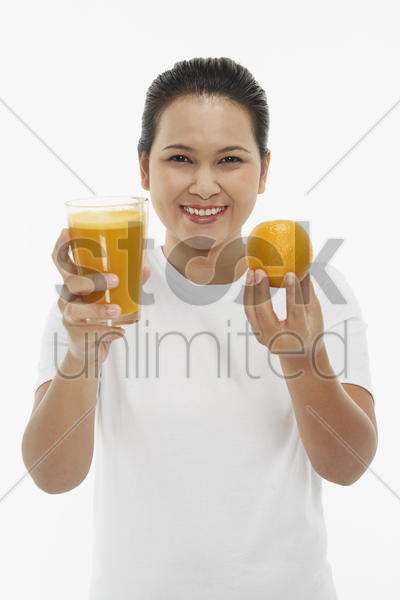 cheerful woman holding up a glass of orange juice stock photo