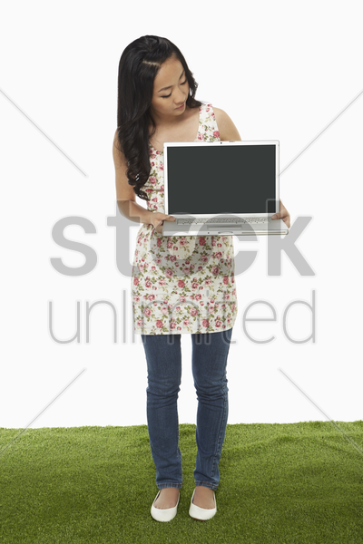 cheerful woman holding up a laptop stock photo