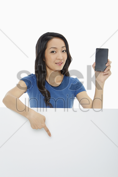 cheerful woman holding up a mobile phone and pointing stock photo