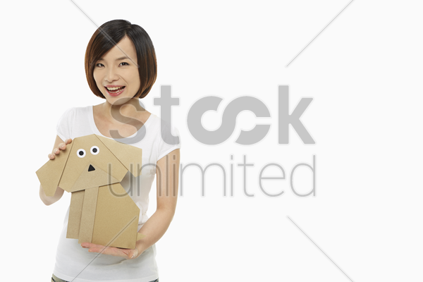 cheerful woman holding up a paper dog stock photo