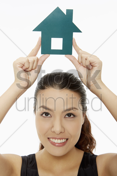 cheerful woman holding up a paper house stock photo