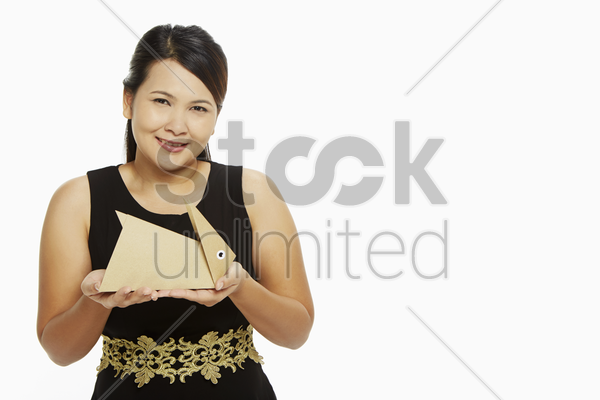 cheerful woman holding up a paper rabbit stock photo