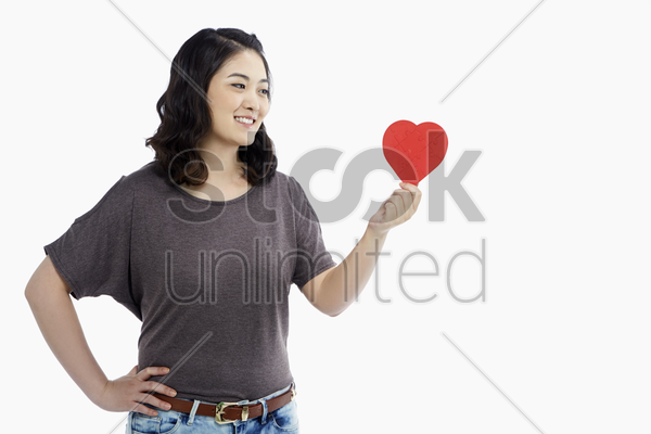 cheerful woman holding up a red heart shape stock photo
