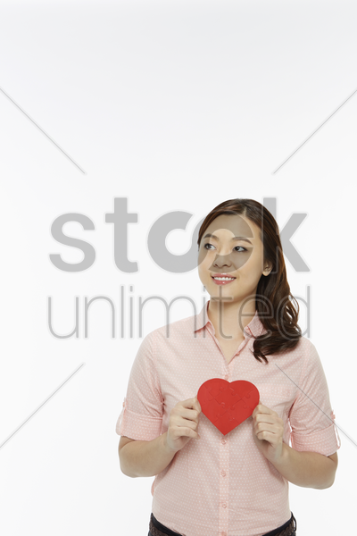 cheerful woman holding up a red heart stock photo