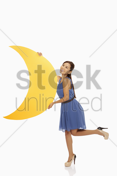 cheerful woman holding up a yellow crescent moon stock photo
