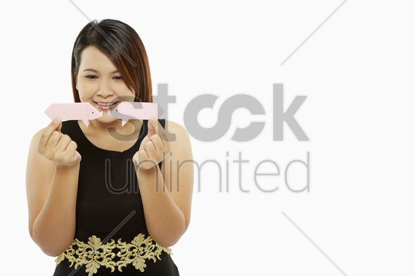 cheerful woman holding up two paper pigs stock photo
