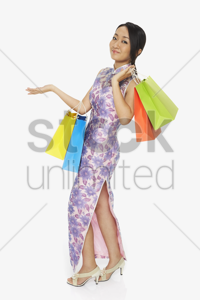 cheerful woman in traditional clothing carrying colorful paper bags stock photo