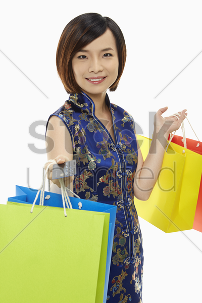 cheerful woman in traditional clothing carrying paper bags stock photo