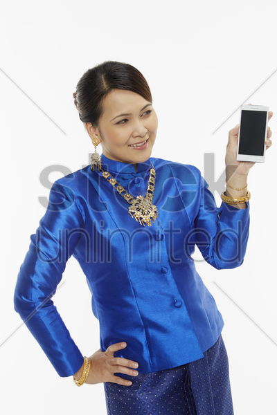 cheerful woman in traditional clothing holding up a mobile phone stock photo
