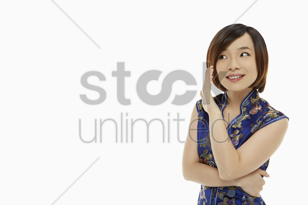 cheerful woman in traditional clothing showing a whispering hand gesture stock photo