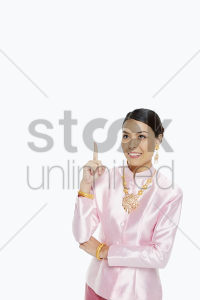 cheerful woman in traditional clothing showing hand gesture stock photo