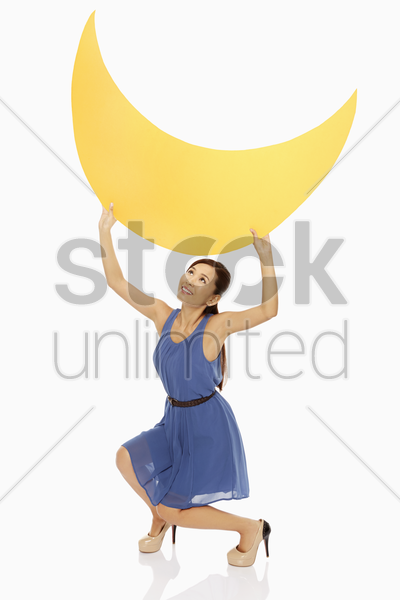 cheerful woman lifting up a yellow crescent moon stock photo