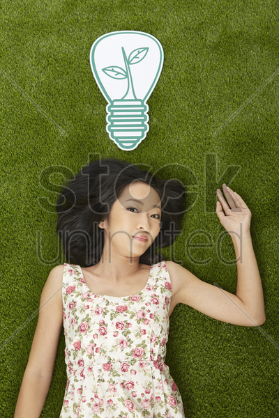 cheerful woman lying on the grass stock photo