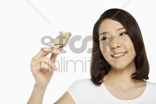 cheerful woman playing with a paper bird stock photo