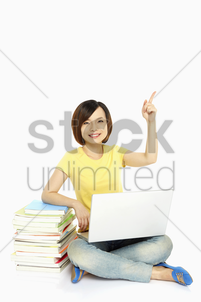 cheerful woman pointing upwards stock photo