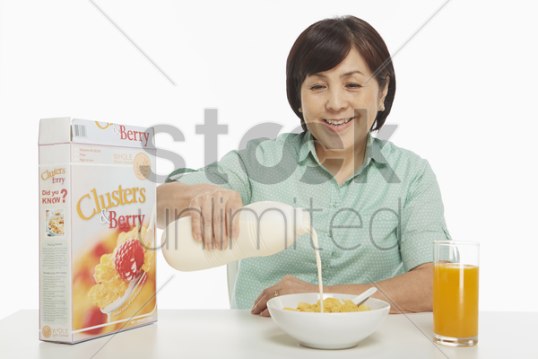 cheerful woman pouring milk into a bowl of cereals stock photo